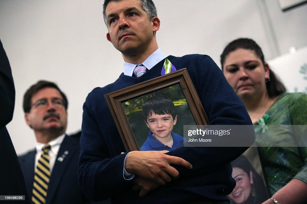 Ian Hockley holds a photo of his son Dylan Hockley (6), embrace during a press conference with fellow parents of victims on the one month anniversary of the Newtown elementary school massacre on January 14, 2013 in Newtown, Connecticut. Eleven families of Sandy Hook massacre victims came to the event one month after the shooting to give their support to Sandy Hook Promise, a new non-profit with the goal of preventing such tragedies in the future.