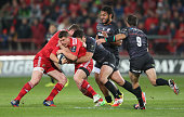 Ian Keatley of Munster is tackled by Brad Barritt during the European Rugby Champions Cup match between Munster and Saracens at Thomond Park on...