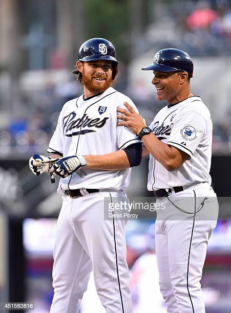 Ian Kennedy of the San Diego Padres is congratulated by first base coach Jose Valentin after hitting an RBI single during the second inning of a...