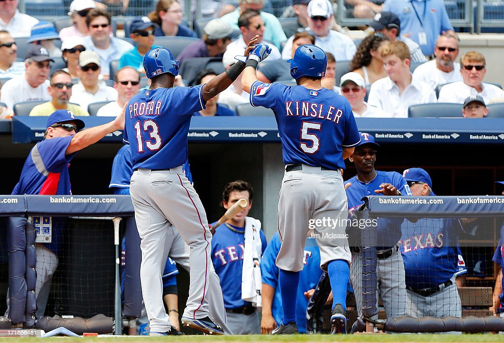 Ian Kinsler #5 and Jurickson Profar #13 of the Texas Rangers celebrate in the third inning after Profar scored against the New York Yankees on a scafrifice fly by Kinsler at Yankee Stadium on June 27, 2013 in the Bronx borough of New York City.