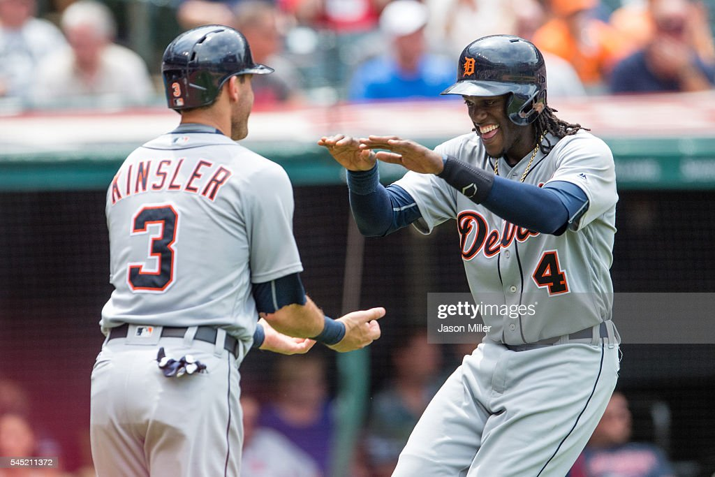 Ian Kinsler celebrates with Cameron Maybin of the Detroit Tigers after both scored on a double by Nick Castellanos of the Detroit Tigers during the...