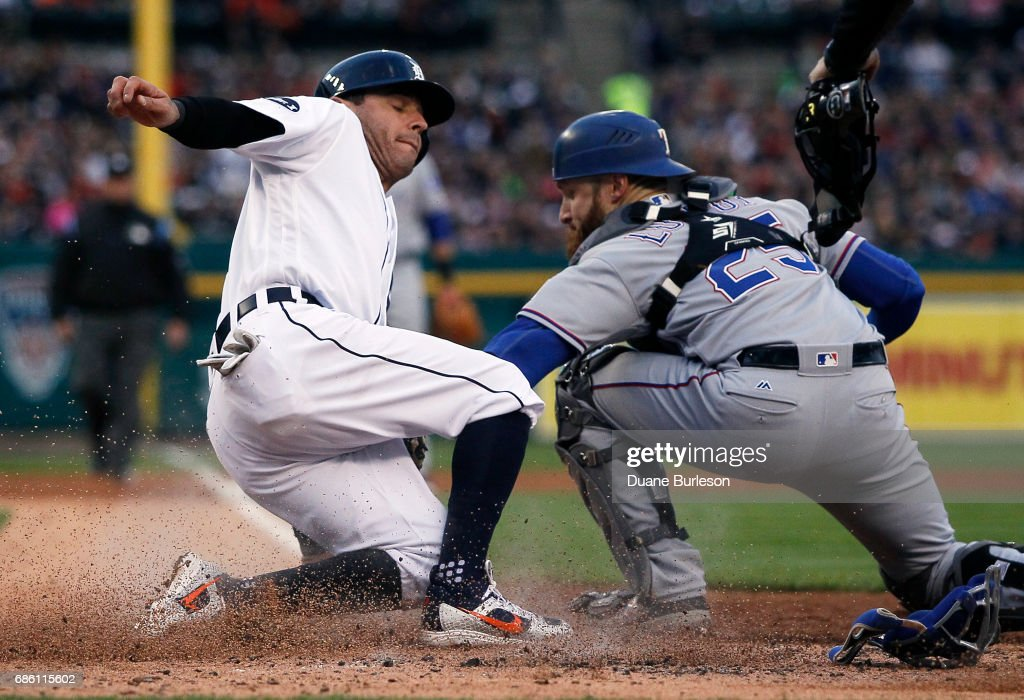 Ian Kinsler #3 of the Detroit Tigers beats the tag from catcher Jonathan Lucroy #25 of the Texas Rangers to score from third base on a ground out by Miguel Cabrera during the third inning at Comerica Park on May 20, 2017 in Detroit, Michigan.