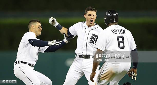 Ian Kinsler of the Detroit Tigers celebrates a game winning single with teammate Jose Iglesias and Justin Upton in the tenth inning giving the Tigers...