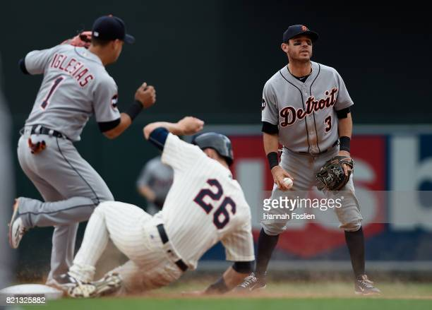 Ian Kinsler of the Detroit Tigers reacts as Max Kepler of the Minnesota Twins reaches second base safely against teammate Jose Iglesias during the...