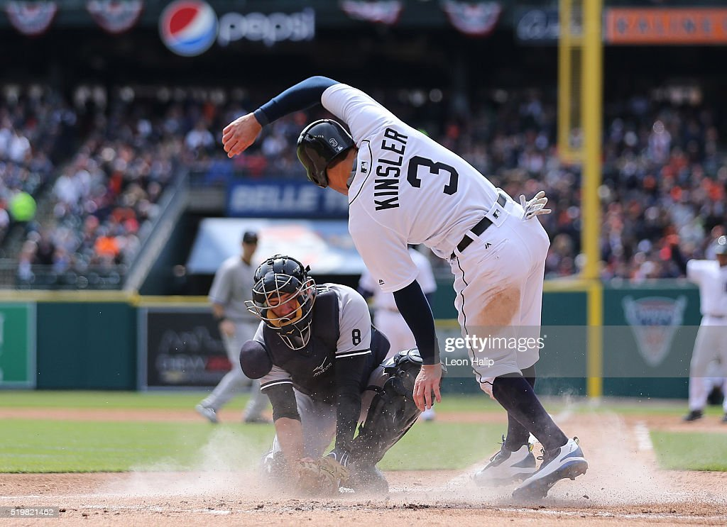 Ian Kinsler of the Detroit Tigers slides home safe on the Miguel Cabrera single to right field as Austin Romine of the New York Yankees attempts to...