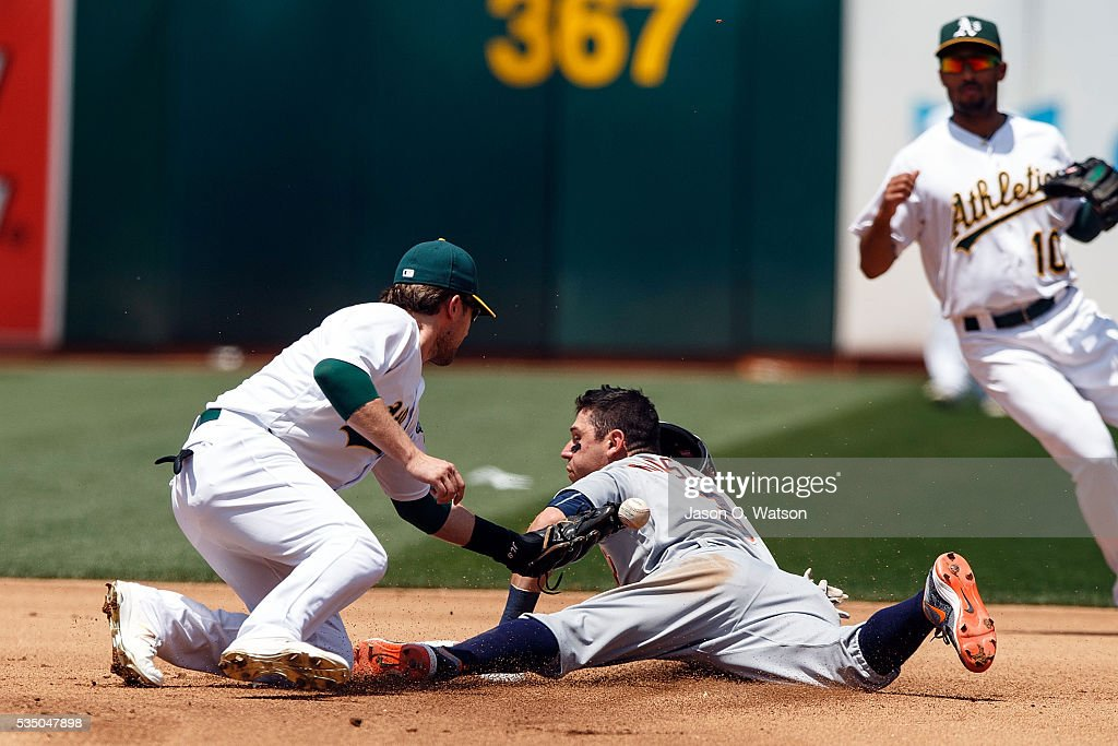 Ian Kinsler of the Detroit Tigers steals second base ahead of a tag from Jed Lowrie of the Oakland Athletics during the fourth inning at the Oakland...