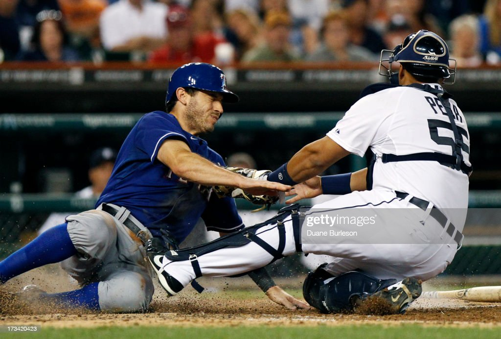 Ian Kinsler of the Texas Rangers avoids the tag from catcher Brayan Pena of the Detroit Tigers to score from second base on an infield single in the...