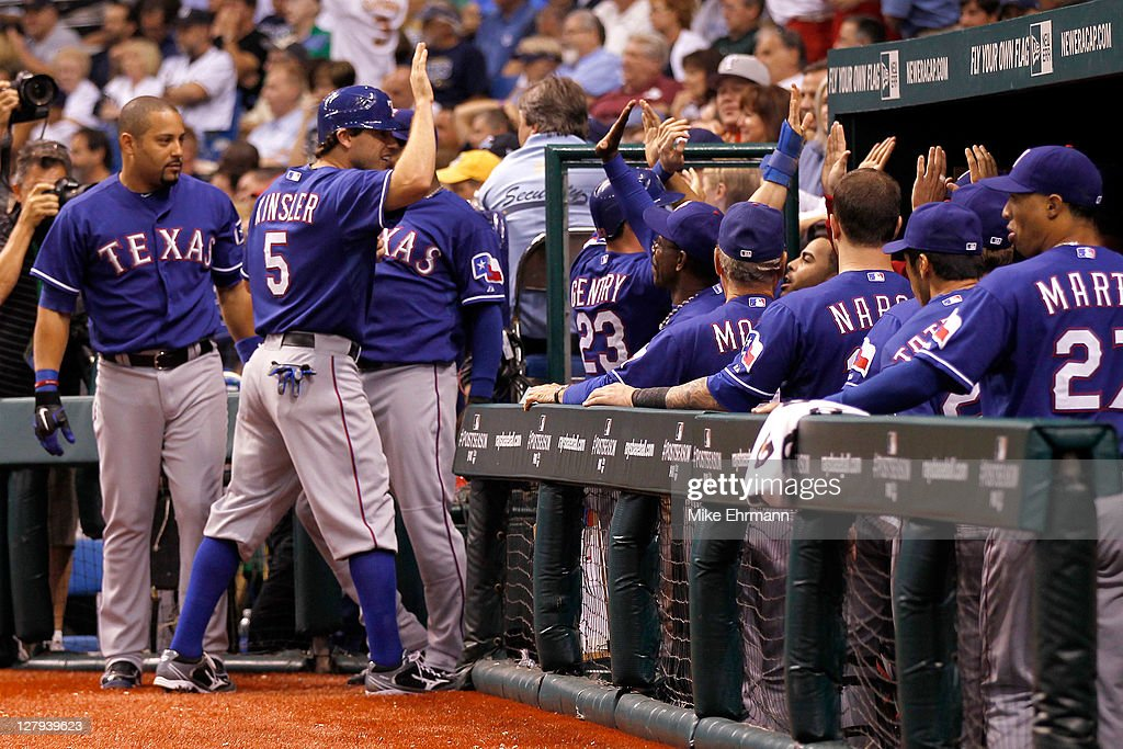 Ian Kinsler of the Texas Rangers celebrates with teammates after scoring in the seventh inning against the Tampa Bay Rays in Game Three of the...