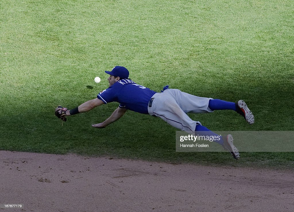 Ian Kinsler #5 of the Texas Rangers dives for a single hit by Oswaldo Arcia #31 of the Minnesota Twins during the eighth inning of the game on April 27, 2013 at Target Field in Minneapolis, Minnesota. The Twins defeated the Rangers 7-2.