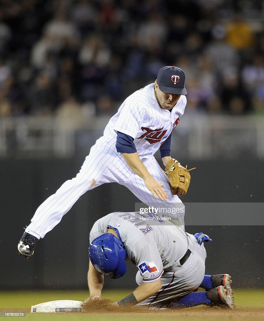 Ian Kinsler #5 of the Texas Rangers is out at second base as Brian Dozier #2 of the Minnesota Twins turns a double play during the fifth inning of the game on April 26, 2013 at Target Field in Minneapolis, Minnesota.