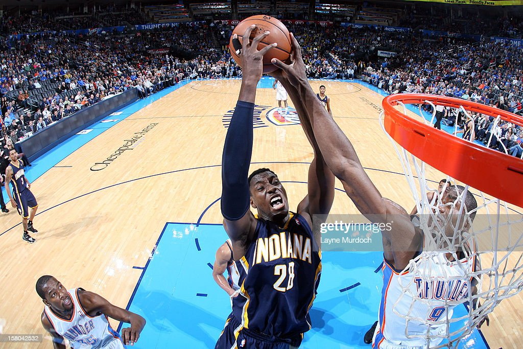 <a gi-track='captionPersonalityLinkClicked' href=/galleries/search?phrase=Ian+Mahinmi&family=editorial&specificpeople=740196 ng-click='$event.stopPropagation()'>Ian Mahinmi</a> #28 of the Indiana Pacers goes to the basket against <a gi-track='captionPersonalityLinkClicked' href=/galleries/search?phrase=Serge+Ibaka&family=editorial&specificpeople=5133378 ng-click='$event.stopPropagation()'>Serge Ibaka</a> #9 of the Oklahoma City Thunder during the game between the Oklahoma City Thunder and the Indiana Pacers on December 9, 2012 at the Chesapeake Energy Arena in Oklahoma City, Oklahoma.