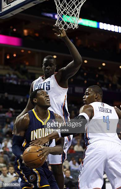 Ian Mahinmi of the Indiana Pacers is hit as he goes to the basket against teammates DeSagana Diop of the Charlotte Bobcats and Jeff Adrien during...