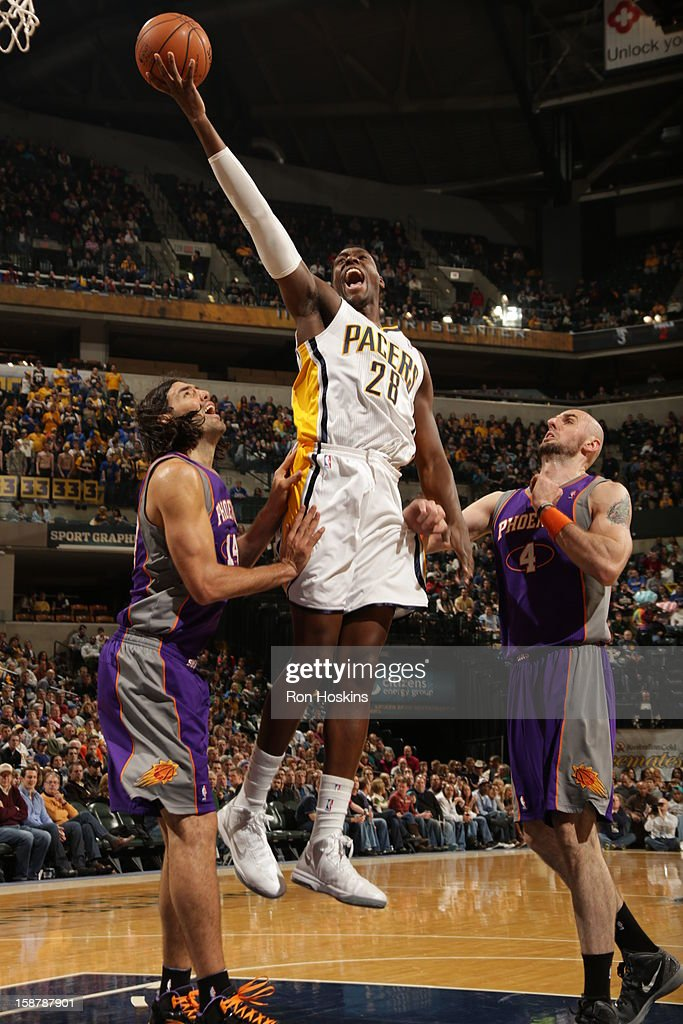 <a gi-track='captionPersonalityLinkClicked' href=/galleries/search?phrase=Ian+Mahinmi&family=editorial&specificpeople=740196 ng-click='$event.stopPropagation()'>Ian Mahinmi</a> #28 of the Indiana Pacers shoots a layup against <a gi-track='captionPersonalityLinkClicked' href=/galleries/search?phrase=Luis+Scola&family=editorial&specificpeople=2464749 ng-click='$event.stopPropagation()'>Luis Scola</a> #14 and <a gi-track='captionPersonalityLinkClicked' href=/galleries/search?phrase=Marcin+Gortat&family=editorial&specificpeople=589986 ng-click='$event.stopPropagation()'>Marcin Gortat</a> #4 of the Phoenix Suns on December 28, 2012 at Bankers Life Fieldhouse in Indianapolis, Indiana.