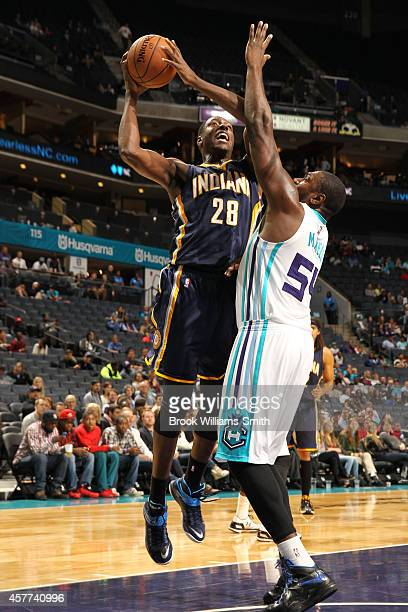 Ian Mahinmi of the Indiana Pacers shoots against Jason Maxiell of the Charlotte Hornets during the game at the Time Warner Cable Arena on October 23...