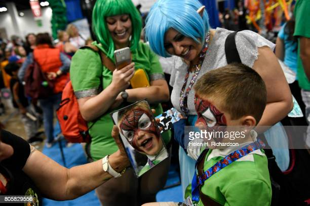 Ian Onstott checks out his SpiderMan face paint with his mother Jenn second from right and his aunt Sarah Onstott middle after having it painted by...