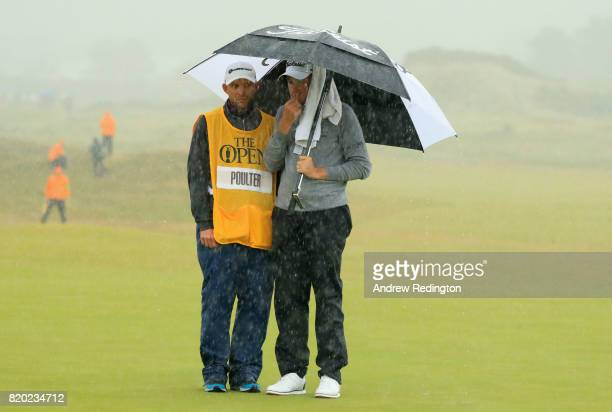 Ian Poulter of England and caddie shelter under an umbrella on the 16th hole during the second round of the 146th Open Championship at Royal Birkdale...