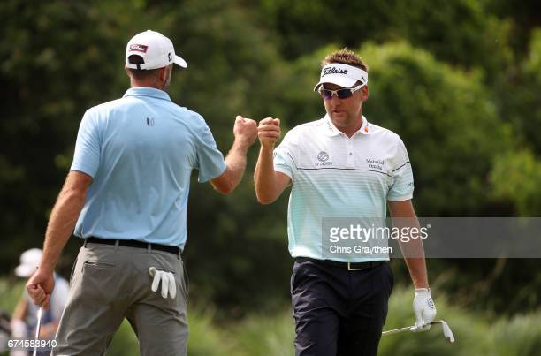 Ian Poulter of England and Geoff Ogilvy of Australia react after their putt on the 14th hole during the second round of the Zurich Classic at TPC...