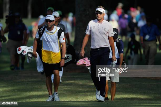 Ian Poulter of England and his caddie James Walton walk on the 15th hole during the final round of THE PLAYERS Championship at the Stadium course at...