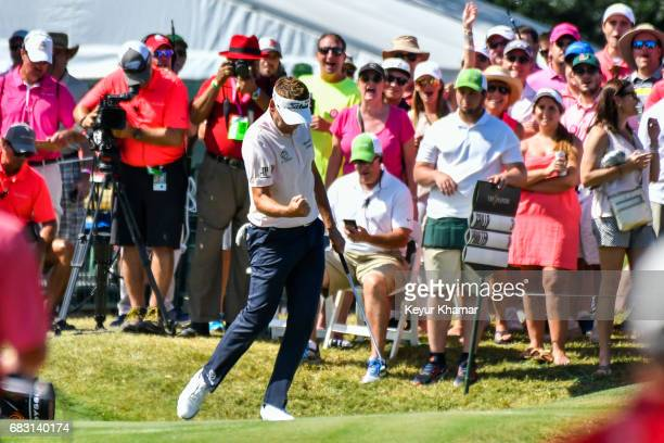 Ian Poulter of England celebrates and pumps his fist after making a long par putt on the ninth hole green during the final round of THE PLAYERS...