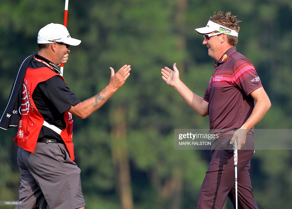 Ian Poulter of England (R) celebrates with his caddy after winning the WGC-HSBC Champions tournament held on the Olazabal Course at the Mission Hill Golf Club in Dongguan on November 4, 2012. Poulter finished on 21 under par. AFP PHOTO/Mark RALSTON