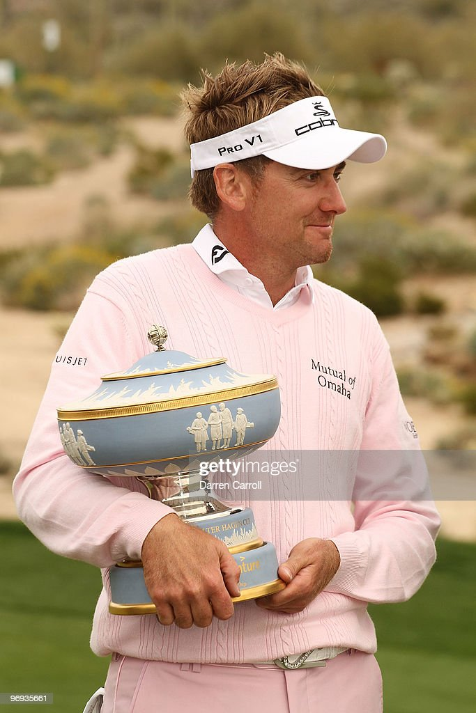 Ian Poulter of England lifts the Walter Hagen Cup trophy on the 16th hole after winning the final round of the Accenture Match Play Championship at...