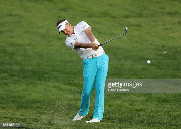 Ian Poulter of England plays his second shot to the par 5 10th hole during the first round of the 2017 Omega Dubai Desert Classic on the Majlis...