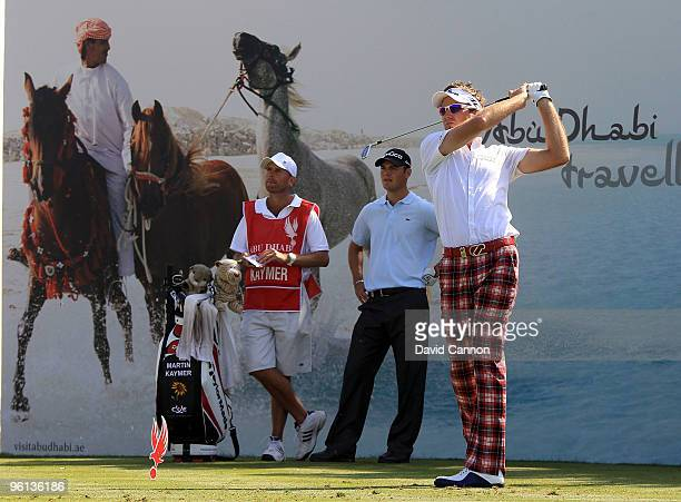 Ian Poulter of England plays his tee shot at the par 3 7th hole watched by Martin Kaymer of Germany during the final round of The Abu Dhabi Golf...