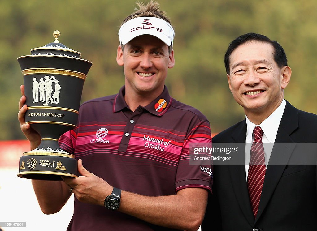 Ian Poulter of England poses with the trophy beside HSBC's Peter Wong (R) after winning the WGC HSBC Champions during the final round at the Mission Hills Resort on November 4, 2012 in Shenzhen, China.