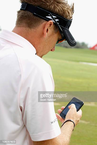 Ian Poulter of England sends a message on Twitter on the practice ground during the final round of the 2011 Abu Dhabi HSBC Golf Championship at the...
