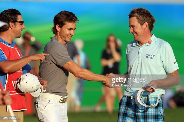 Ian Poulter of England shakes hands with Camilo Villegas of Colombia after Poulter had holed a huge birdie putt at the par 5 18th hole during the...