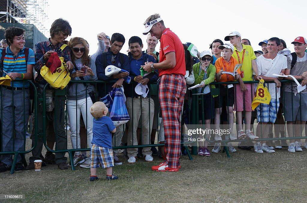 Ian Poulter of England signs autographs as son Joshua looks on during the second round of the 142nd Open Championship at Muirfield on July 19, 2013 in Gullane, Scotland.
