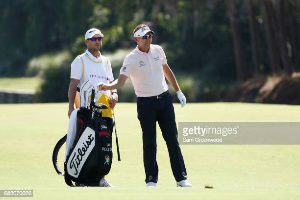 Ian Poulter of England talks with his caddie James Walton on the tenth hole during the final round of THE PLAYERS Championship at the Stadium course...