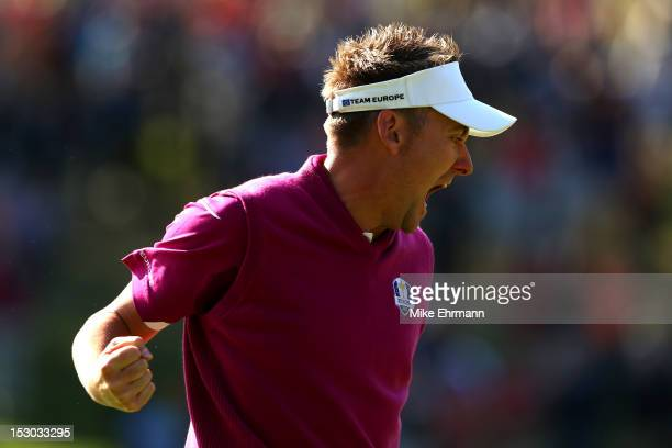 Ian Poulter of Europe celebrates after holing a putt on the 12th hole during day two of the Morning Foursome Matches for The 39th Ryder Cup at...