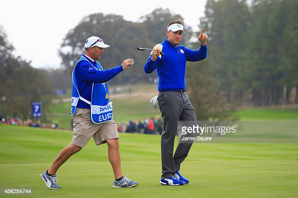 Ian Poulter of Europe celebrates after winning the 7th hole with caddie Terry Mundy during the Singles Matches of the 2014 Ryder Cup on the PGA...