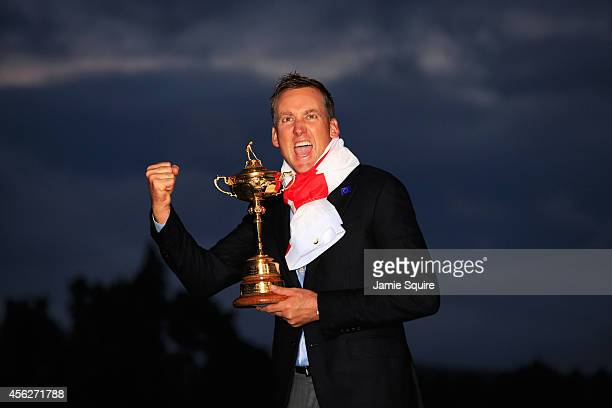 Ian Poulter of Europe celebrates with the Ryder Cup trophy after the Singles Matches of the 2014 Ryder Cup on the PGA Centenary course at the...