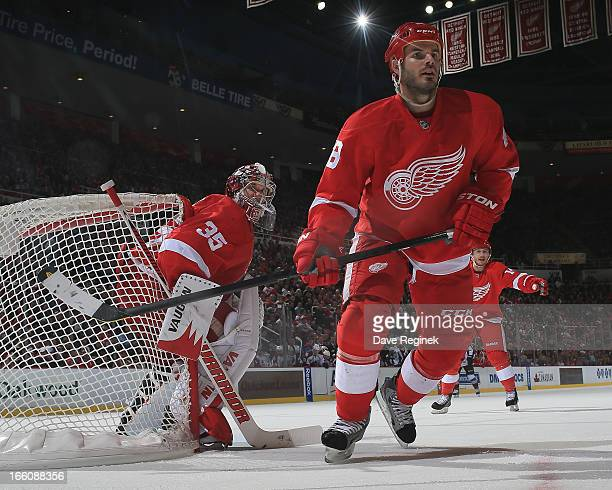 Ian White and Jimmy Howard of the Detroit Red Wings follow the play during a NHL game against the Colorado Avalanche at Joe Louis Arena on April 1...