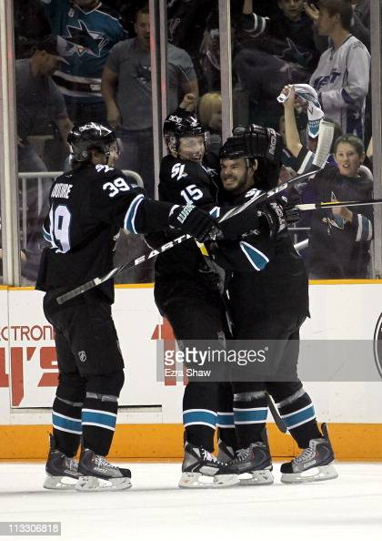 Ian White is congratulated by Dany Heatley and Logan Couture of the San Jose Sharks after he scored a goal in the first period against the Detroit...