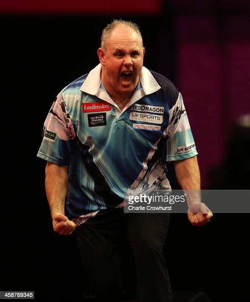Ian White of England celebrates winning his second round match against Kim Huybrechts of Belgium during the Ladbrokescom World Darts Championship on...