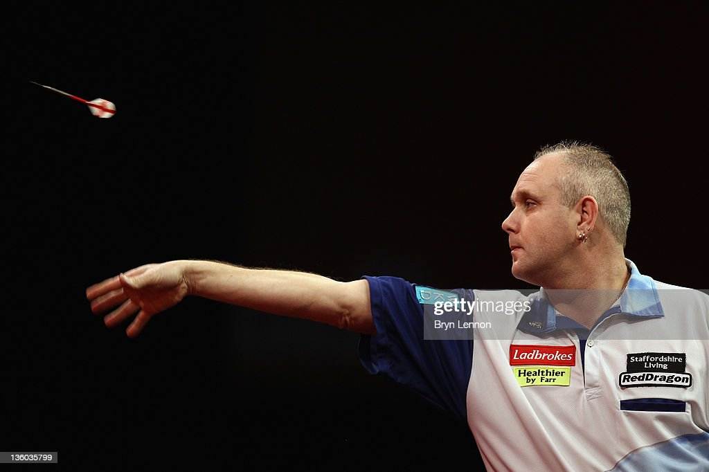 Ian White of Great Britain throws against Robert Thornton of Great Britain during day three of the 2012 Ladbrokescom World Darts Championship at...
