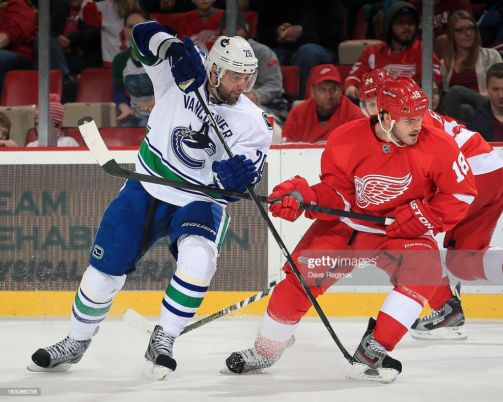 Ian White #18 of the Detroit Red Wings battles for position with Chris Higgins #20 of the Vancouver Canucks during a NHL game at Joe Louis Arena on February 24, 2013 in Detroit, Michigan. The Wings won 8-3