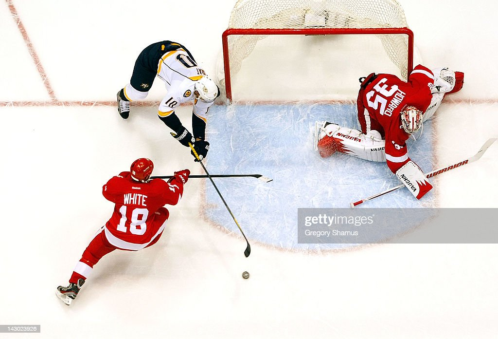 Ian White #18 of the Detroit Red Wings battles for the puck with <a gi-track='captionPersonalityLinkClicked' href=/galleries/search?phrase=Martin+Erat&family=editorial&specificpeople=210561 ng-click='$event.stopPropagation()'>Martin Erat</a> #10 of the Nashville Predators with <a gi-track='captionPersonalityLinkClicked' href=/galleries/search?phrase=Jimmy+Howard&family=editorial&specificpeople=2118637 ng-click='$event.stopPropagation()'>Jimmy Howard</a> #35 looking on during Game Four of the Western Conference Quarterfinals during the 2012 NHL Stanley Cup Playoffs at Joe Louis Arena on April 17, 2012 in Detroit, Michigan. Nashville won the game 3-1 and lead the series 3-1.