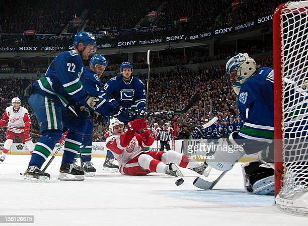 Ian White of the Detroit Red Wings is surrounded by Daniel Sedin Roberto Luongo Sami Salo and Alexander Edler of the Vancouver Canucks during a NHL...
