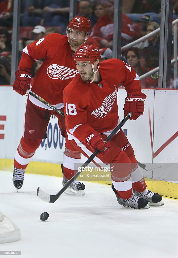 Ian White #18 of the Detroit Red Wings skates out with the puck behind his own net as Jakub Kindl #4 follows during an NHL game against the Chicago Blackhawks at Joe Louis Arena on March 31, 2013 in Detroit, Michigan.