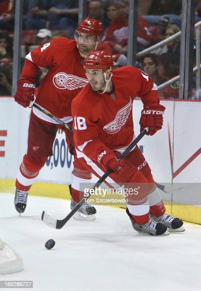 Ian White of the Detroit Red Wings skates out with the puck behind his own net as Jakub Kindl follows during an NHL game against the Chicago...