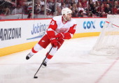 Ian White of the Detroit Red Wings skates with the puck during the NHL game against the Phoenix Coyotes at Jobingcom Arena on March 25 2013 in...
