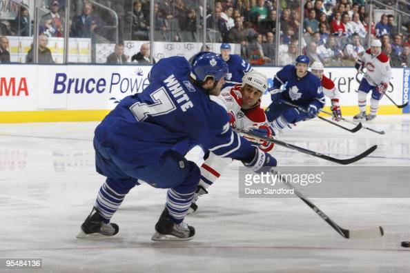 Ian White of the Toronto Maple Leafs makes a pass play under pressure from Scott Gomez of the Montreal Canadiens during their NHL game at the Air...
