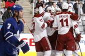 Ian White of the Toronto Maple Leafs skates past as Martin Hanzal of the Phoenix Coyotes celebrates a third period goal with teammates during game...