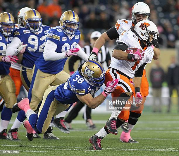 Ian Wild of the Winnipeg Blue Bombers brings down Keola Antolin of the BC Lions in first half action in a CFL game at Investors Group Field on...
