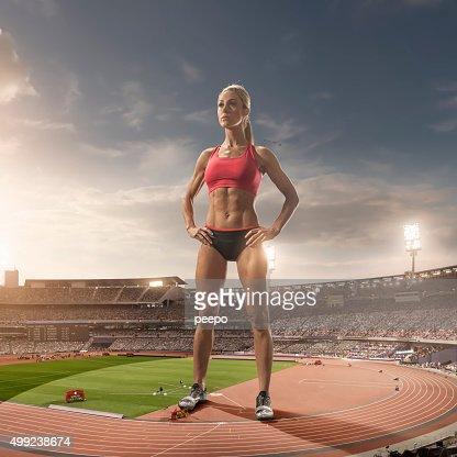 iant Woman Athlete Standing in Floodlit Athletics Stadium