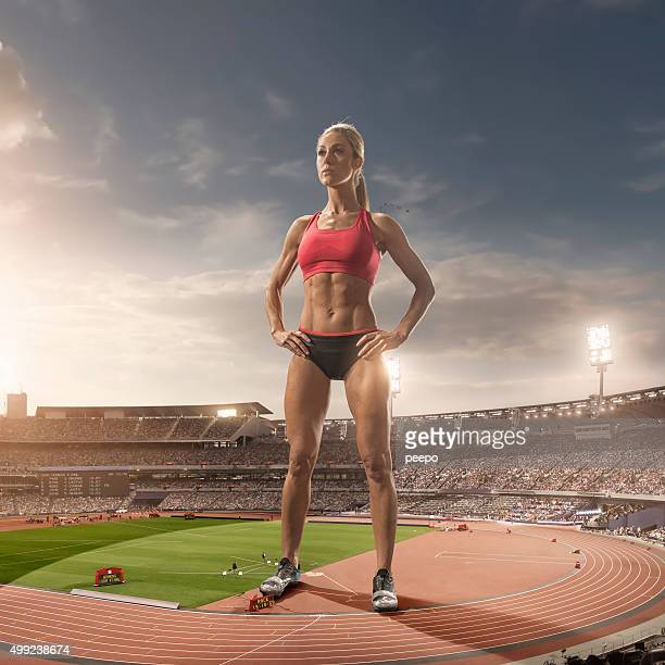 iant Woman Athlete Standing in Floodlit Athletics Stadium